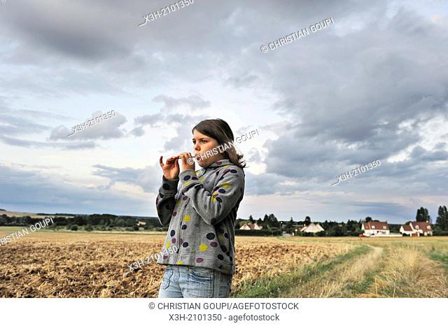teenager playing whistle with a straw in a field, France, Europe