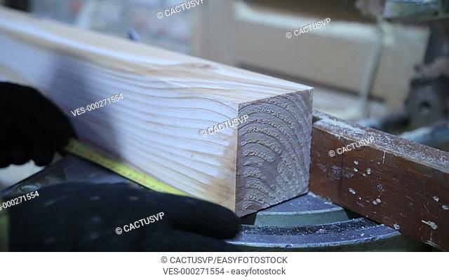 Circular saw cutting wooden plank in workshop