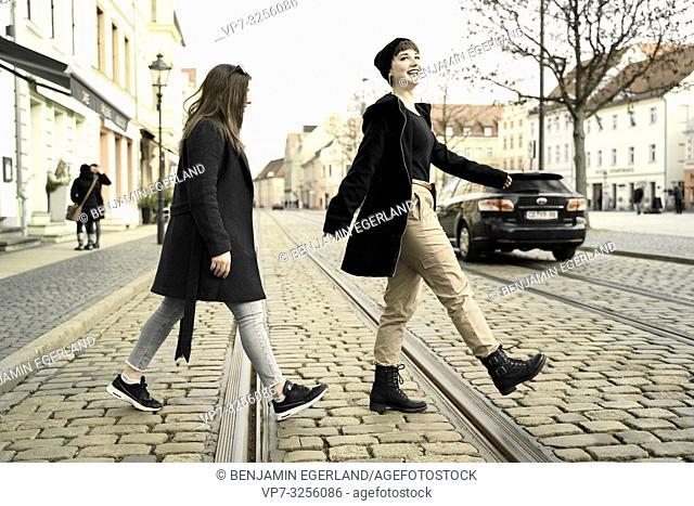 two women crossing street, emulating, walking in city Cottbus, Brandenburg, Germany