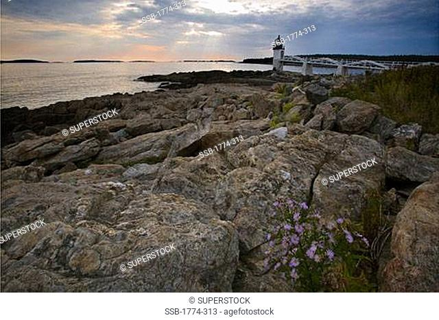 Rock formation at the coast with a lighthouse in the background, Marshall Point Lighthouse, Port Clyde, Maine, USA