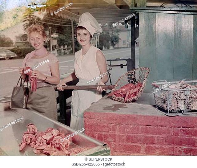 USA, Massachusetts, Essex, Woodman's Lobster Pool, women at seafood stall