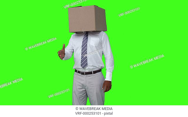 Businessman with box over head shaking hand