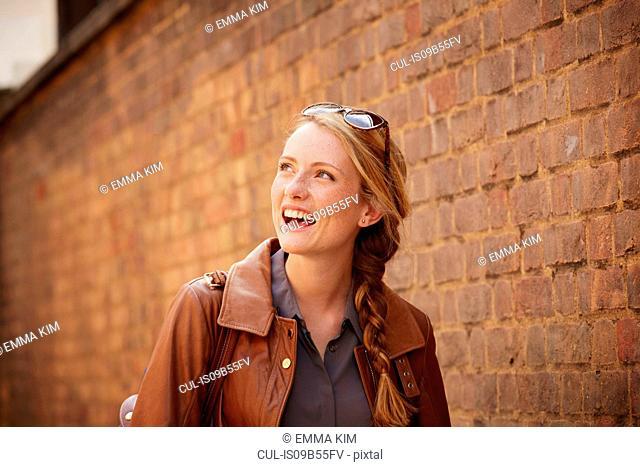 Woman walking along brick wall, London, UK