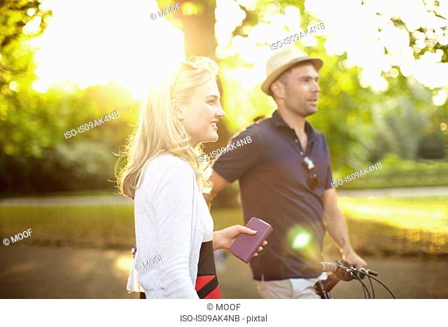 Couple with bicycle strolling in sunlit park