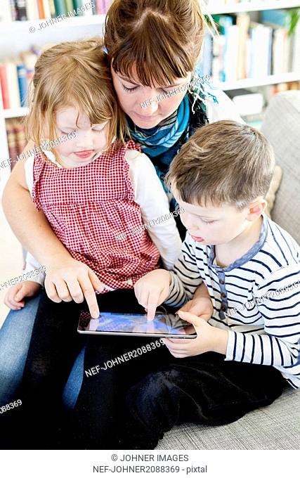 Mother and children vid a tablet