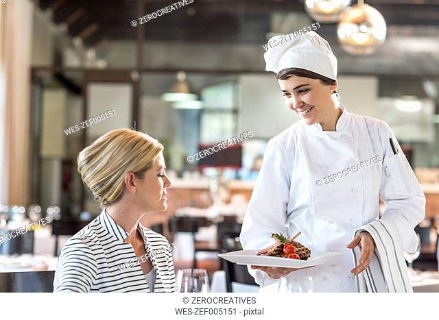 Chef serving food for blonde woman