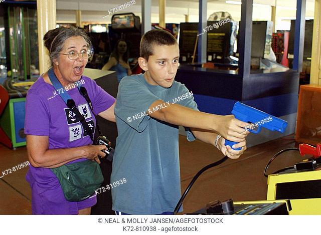 Woman excited by grandson's accuracy at a game in an arcade