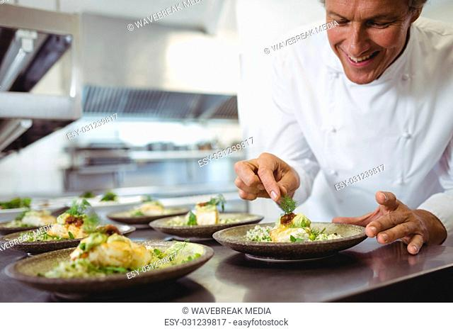 Male chef examining appetizer plates at order station