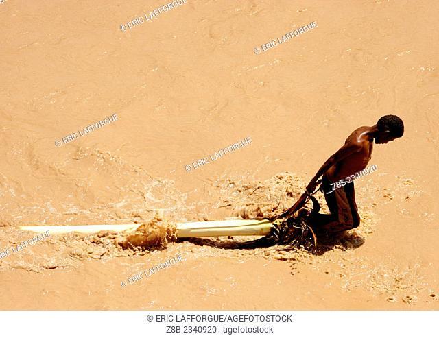 Young Man Pulling A Palm Accross A Muddy Wadi, Tihama, Yemen