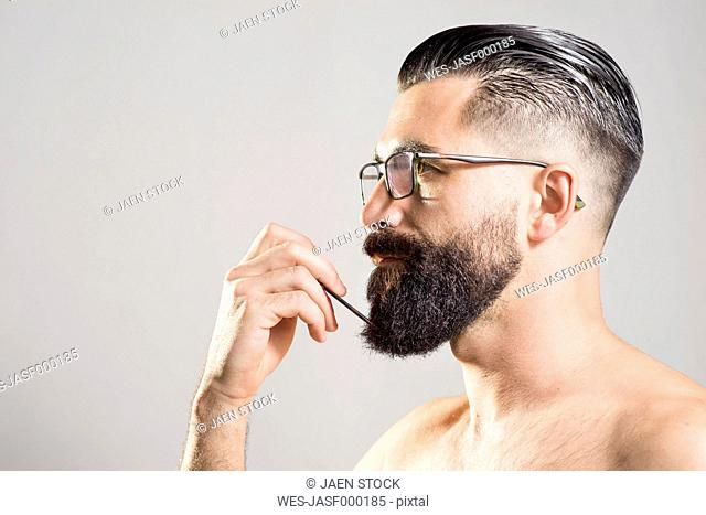 Dark-haired man combing beard