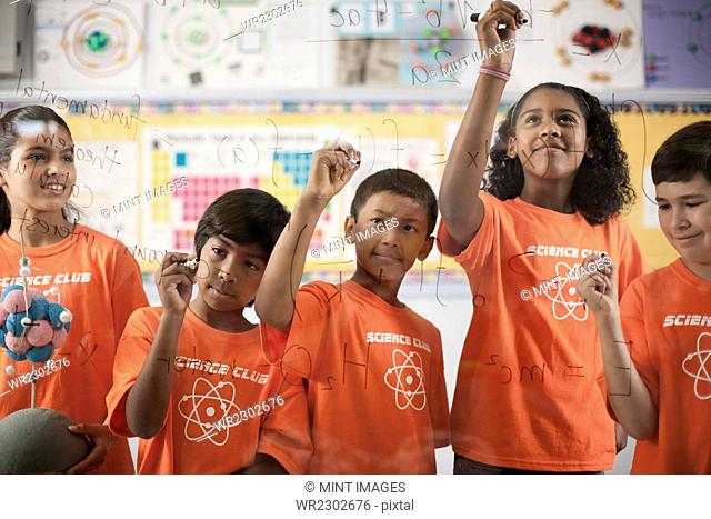 A group of girls and boys wearing the teeshirt of the Science Club writing equations and formulae on a clear board