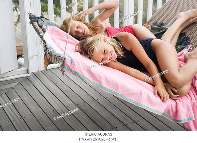 Two girls lying on a porch swing