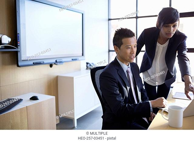 Businessman and businesswoman at laptop in conference room