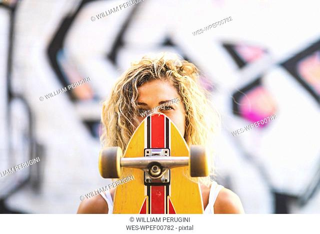 Portrait of young woman with skateboard at graffiti wall