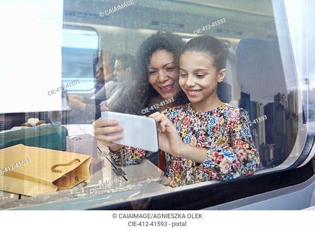 Mother and daughter using camera phone at window of passenger train