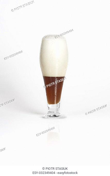 Half of glass of cold dark beer on a white background isolated