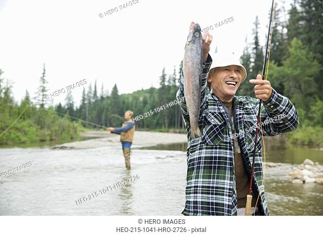 Cheerful senior man holding up fish