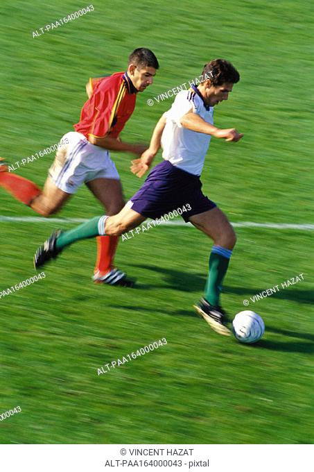 Soccer player running with ball, opponent chasing him, full length, blurred