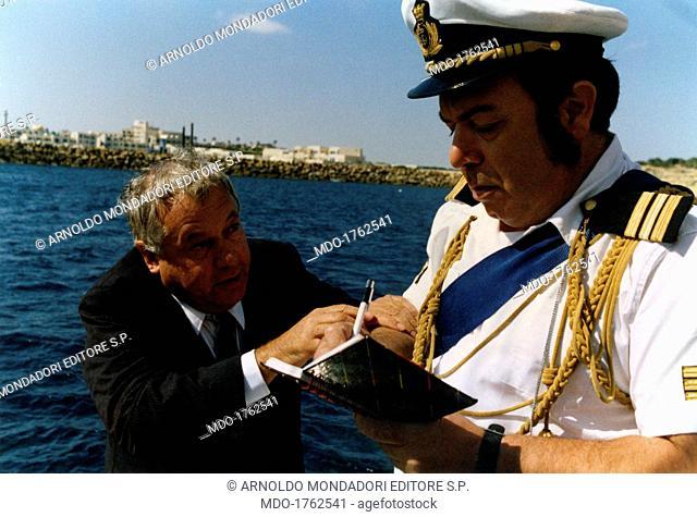Paolo Villaggio and Lino Banfi in Com'è dura l'avventura. Italian actor and comedian Lino Banfi (Pasquale Zagaria) writing the personal details of Italian actor...