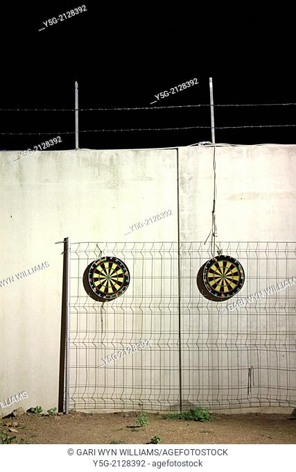 two dart boards on wall outside at night