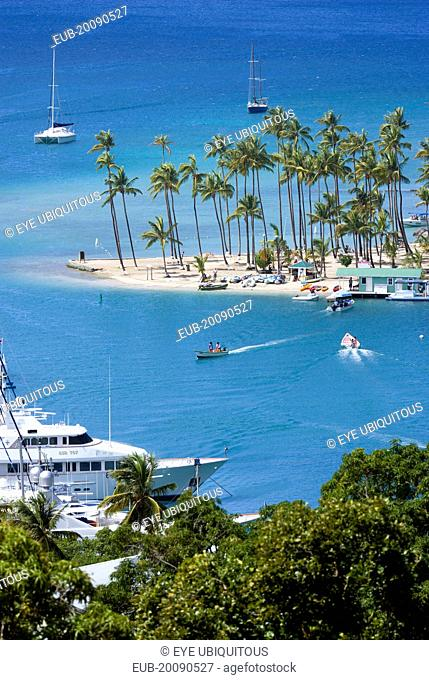 Marigot Bay Yachts at anchor beyond the small coconut palm tree lined beach of the Marigot Beach Club sitting at the entrance