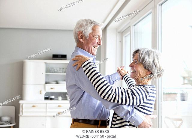 Senior couple dancing together at home at home