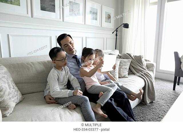 Father and children using digital tablet on living room sofa