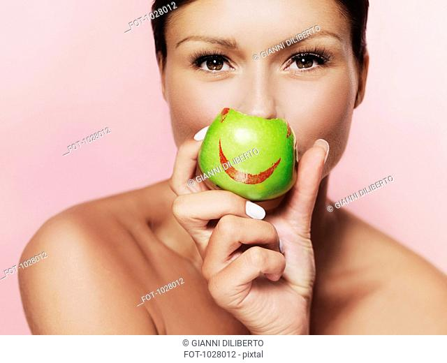 A woman holding up a green apple with bright red lipstick on it