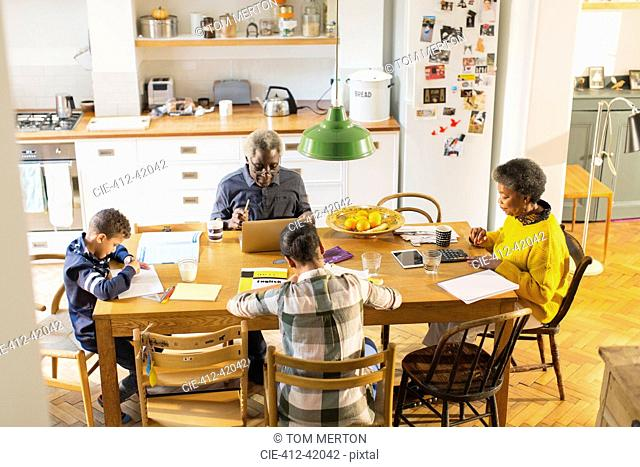 Grandparents at dining table with grandchildren doing homework