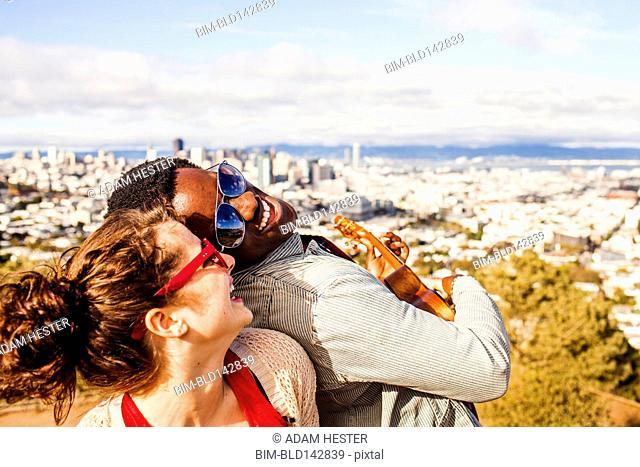 Couple playing ukulele near scenic view of cityscape