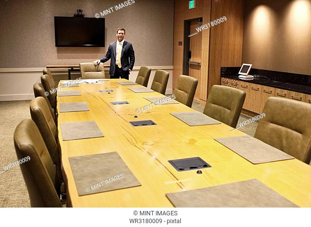 Businessman at the head of a large conference room table