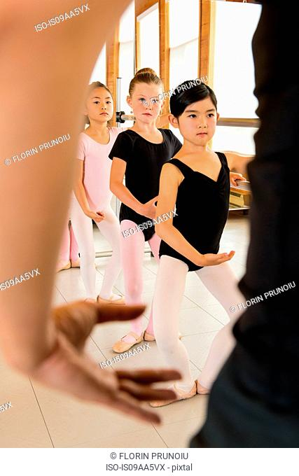 Mature woman teaching ballet dancers in studio