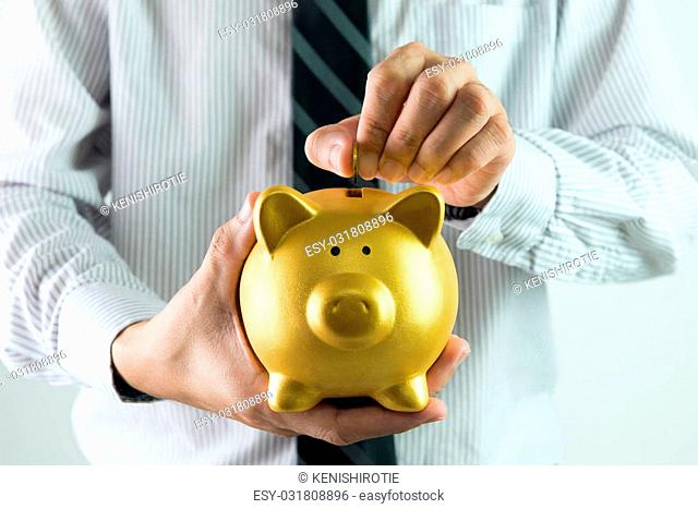 Close up of businessman putting coin into golden piggy bank