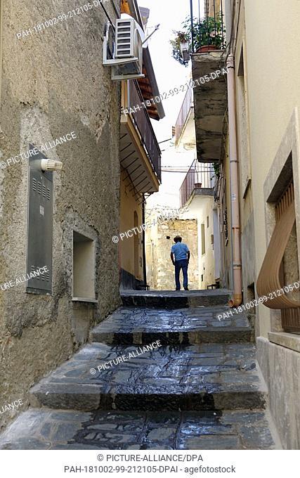 06 September 2018, Italy, Castelmola: 06 September 2018, Italy, Castelmola: An old man walks through an alley in the mountain village of Castelmola