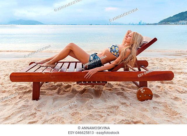 beautiful young slim blonde woman girl gets suntan on a sunbed near the sea