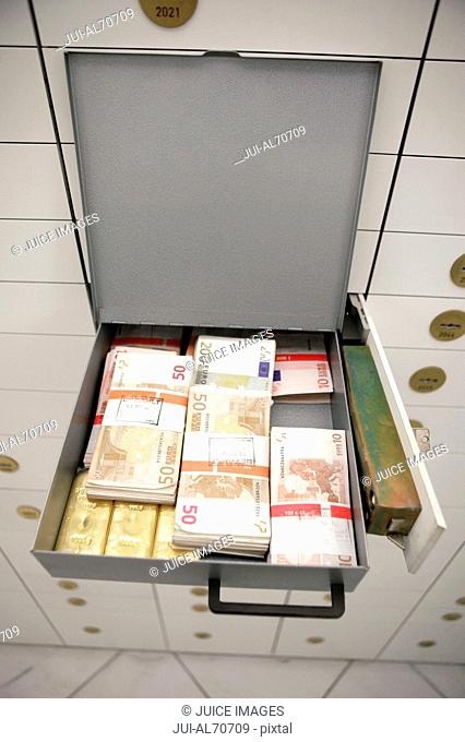 Overview of an open strongbox containing bundles of currency