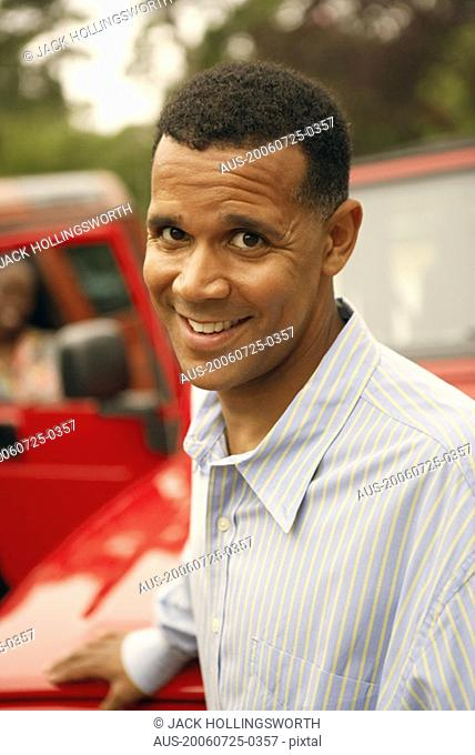 Portrait of a mature man standing near a car and smiling