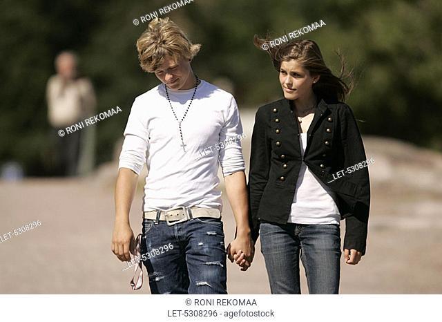 Teenaged girl and boy promenading hand in hand in Kaivopuisto