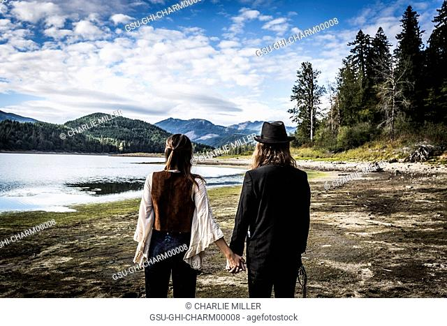 1970s Styled Couple Looking at Scenic Landscape, Rear View, Merrill Lake, Washington, USA