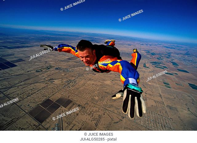 Close-up of skydiving man in colourful costume in mid-air
