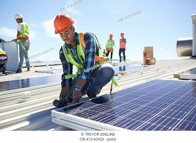Engineer installing solar panels at sunny power plant