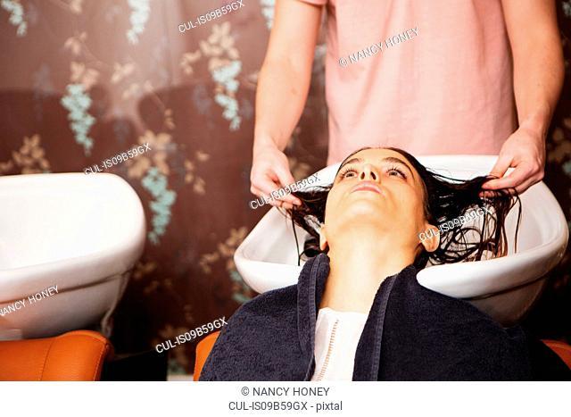 Female customer having hair washed in salon sink