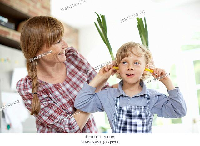 Mother and son playing with vegetable in kitchen