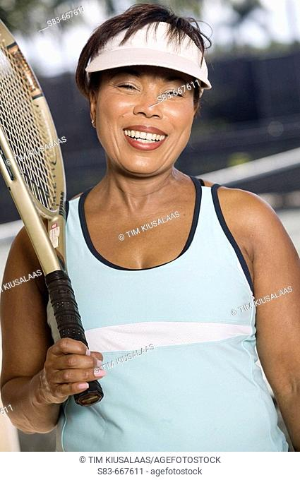 Portrait of a senior woman with a tennis racquet