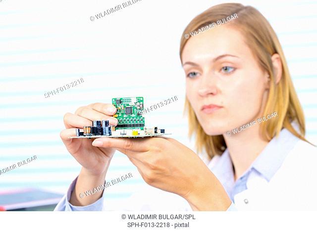 Female electrical engineer fixing circuit board