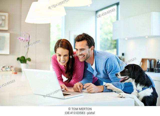 Couple using laptop with dog at table