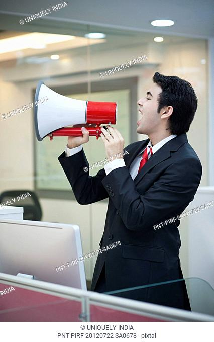 Businessman shouting into a bullhorn