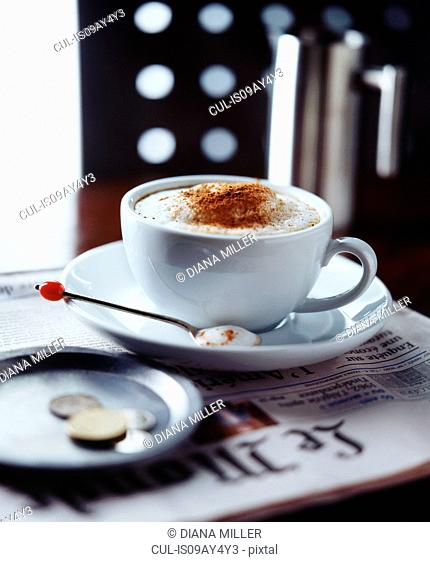 Cappuccino on newspaper in coffee shop