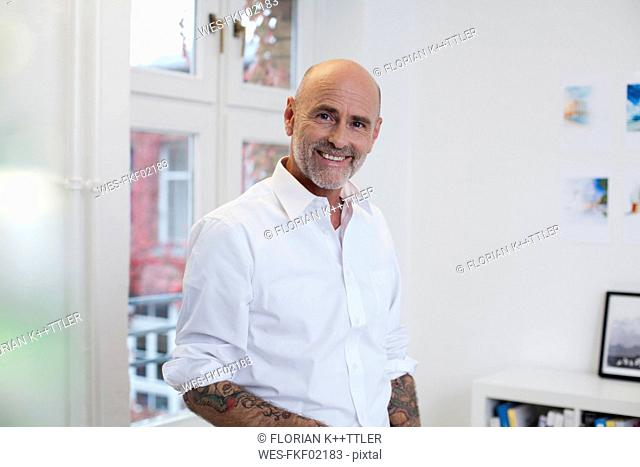 Portrait of smiling tattooed businessman in office
