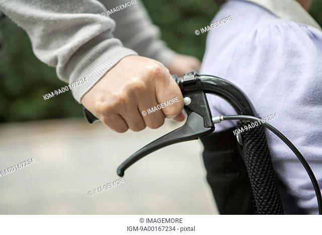 Close-up of human hands pushing wheel-chair